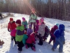 Pre-kindergartners go for a winter walk in the woods.